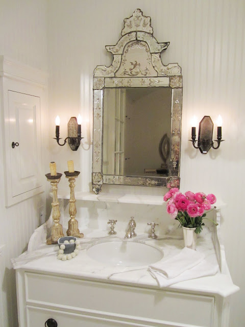 Bathroom in the House of Windsor with white beadboard paneled walls, marble counter top, white cabinets, a vintage etched mirror, two candle sticks, pink peonies and two wall mounted candle stick holder inspired lights