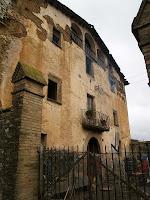 La façana principal amb el portal d'arc rodó, un balcó i l'eixida de la planta sota teulada