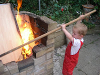 prodding a bonfire with a broomstick