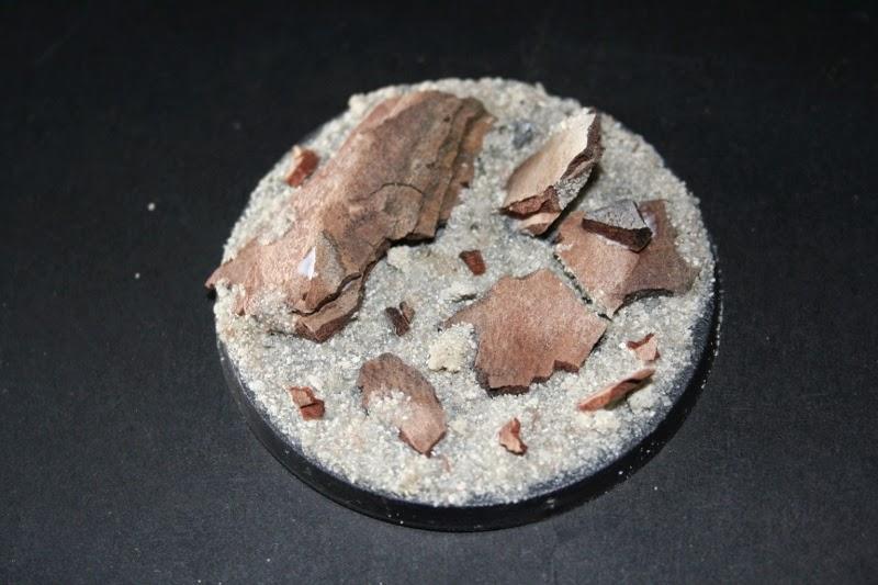 Pegado de la arena y pequeñas rocas en la peana
