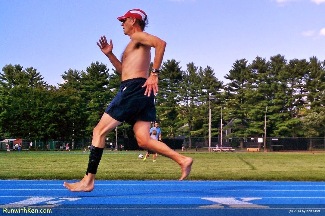 Up-close action photo of a barefoot runner (not in minimalist shoes, but actually barefoot) running--no, FLYING!--six inches above the track in Lexington, MA. Sports Photography by Ken Skier, The Running Photographer. (RunwithKen.com)