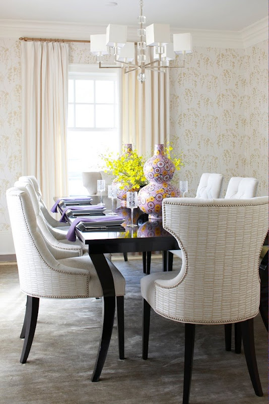 Dining room with floor to ceiling wallpaper, black polished table, floor length cream curtains and white armchairs with nail head trim