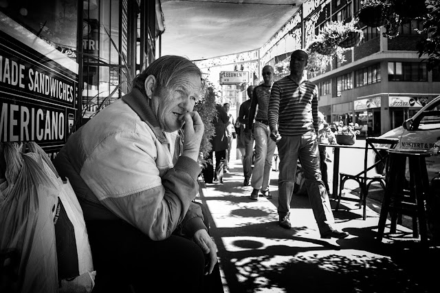A candid street portrait of a man looking worried as other men walk past.