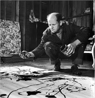 Jackson Pollock painting with a cigarette hanging from his lips.
