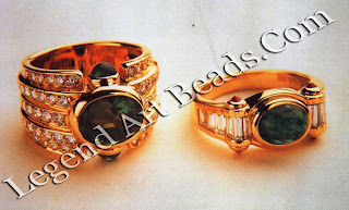 """Two rings in which the central oval emeralds are enhanced by ruby and emerald """"pippoli"""" (small stones embellishing the central gem) in the manner characteristic of Bulgari jewelry."""