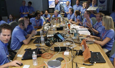 Curiosity MSL lands on Mars. Entry, Descent and Landing (EDL) team in blue shirts. Laptop table. Control room at JPL, 6 August 2012. NASA/JPL.