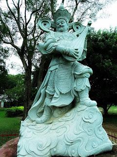 Estátua de pedra de guerreiro tocando alaúde.