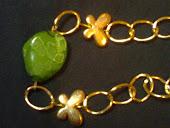 pulseira dourada c pedra verde e borboleta