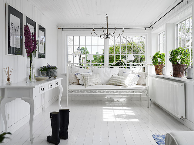 White indoor porch Swedish cottage painted wood floor white wire bench white cushions