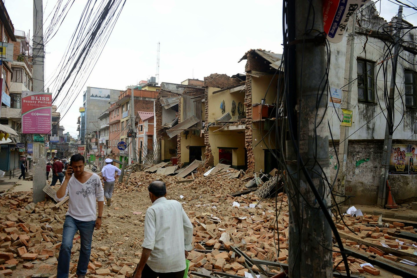 Nepalese people walk past collapsed buildings at Lalitpur