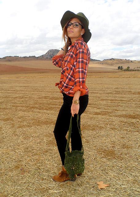 Camisa de cuadros con vaqueros rotos, botas boho, sombrero y bolso