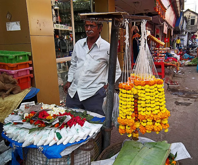 man selling flower garlands