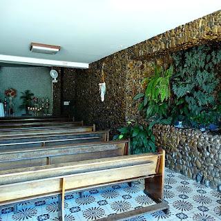 Gruta de Nossa Senhora Aparecida, São Marcos. Construída com pedras de rio. Há bancos de igreja para orações.
