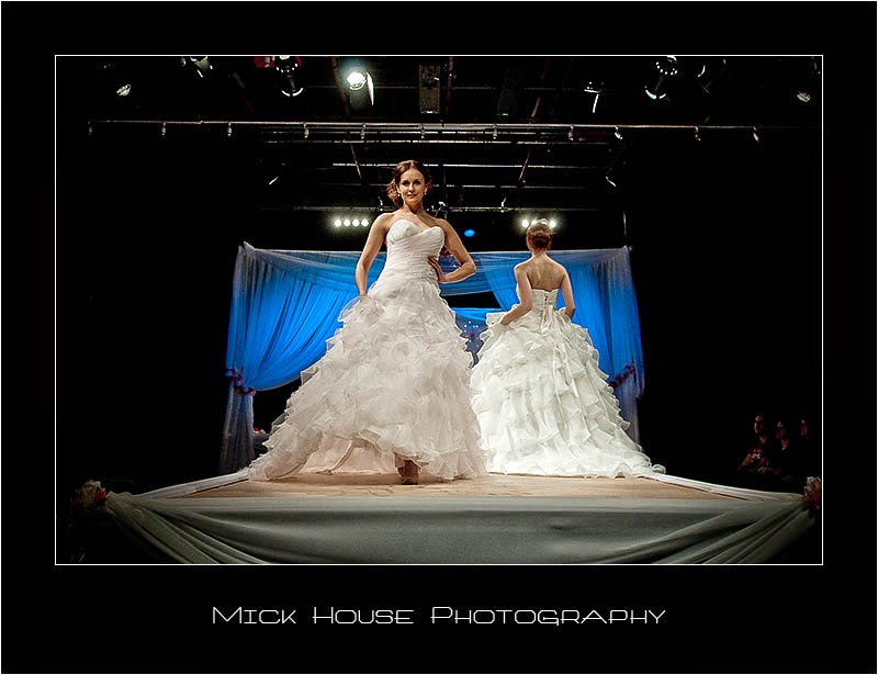 Two models wearing wedding dresses on a catwalk
