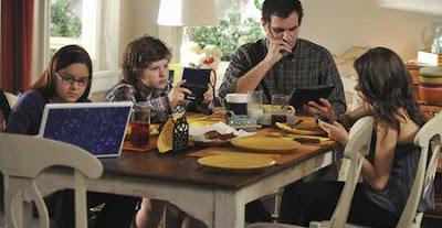 Foto de uma família na mesa, se alimentando. cada um em um computador, vídeogame ou smartphone.