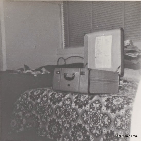 An open suitcase on a bed with a pile of clothes behind
