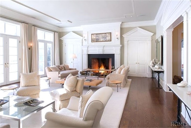 Classic living room in a Bedford, NY home with cream colored armchairs, dueling sofas and hard wood floor