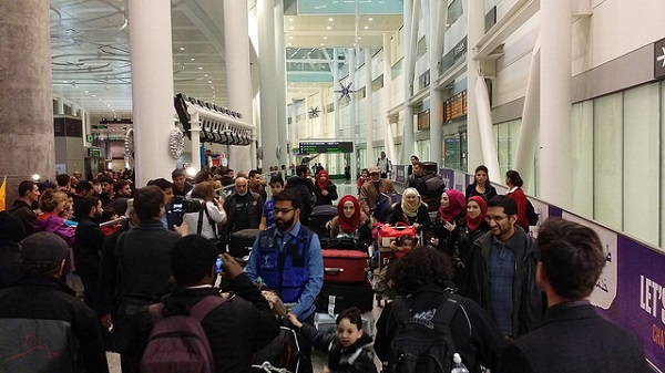A Syrian family at Toronto's Pearson International Airport, amid a crowd of media and onlookers.
