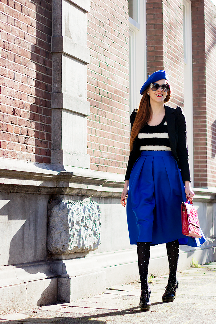 Retro fashion blogger outfit with a cobalt blue midi skirt, beret, striped fluffy top and polka dot tights