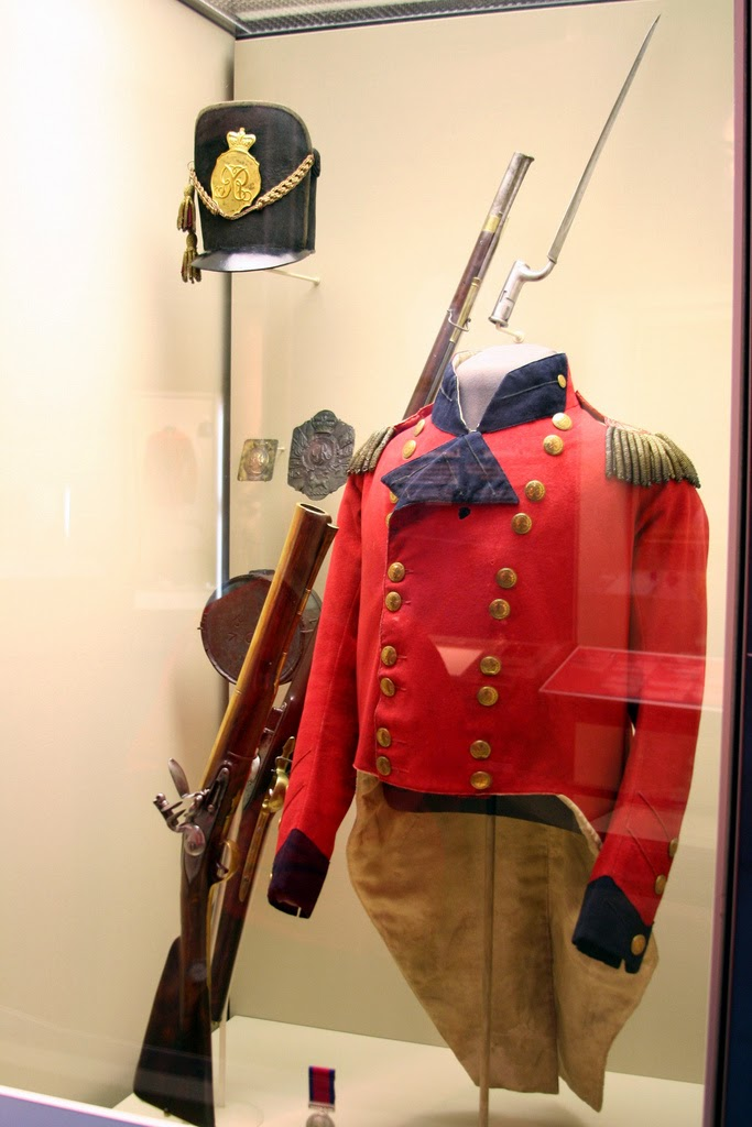Colour photograph of a red military jacket, a rifle, and a hat.