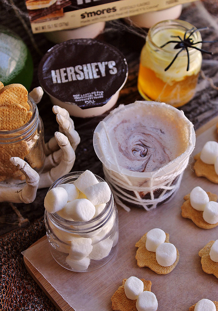 Spooky S'mores Spiderweb Pudding Cups- Are you prepared to #ReadySetSnack with delicious new Hershey's ready-to-eat refrigerated pudding cups from Walmart? Hershey's pudding cups come in delicious flavors such as Chocolate and S'mores and are made with real Hershey's Cocoa. Make these fun s'mores spiders and chocolate webs to help kick off the Halloween season and add a little extra fun to your snack time! Grab the FREE printable template! (ad)