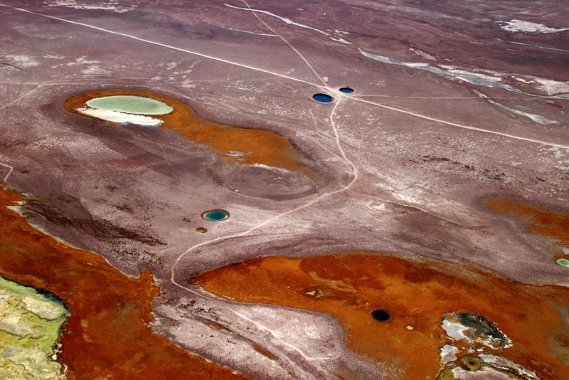 "The Ojos del Salar ""The Eyes of the Salt Flat"" Two perfectly round pools in the middle of a wide expanse of cracked earth, sand and brittle clumps of grass."