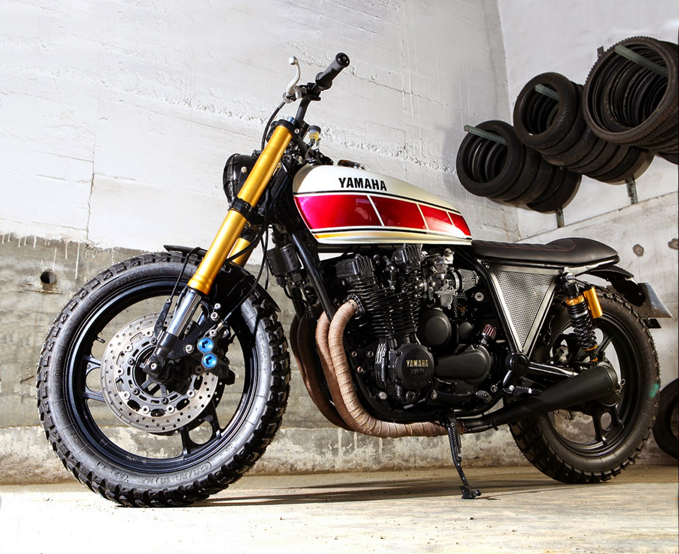 Custom Yamaha Xj 900 Custom Yamaha XJ 900 Scrambler a custom bike from the Tarmac Custom Motorcycles in Spain. This Custom bike stared with a 1986 Yamaha Xj 900 as a base. The Guys at TMC Stripped this Yamaha Xj 900 to essentials. They were not happy with the plastics surrounding this 900cc Japanese machine. The Original take was replaced with Kawasaki Kz650, Gas tank and was painted in retro Yamaha Race livery. The Front suspension and the brakes were borrowed from Yamaha R1.  A Custom Headlamp Grill adds charm, The rear sub Frame was modified to accommodate The custom seat and Handle bar risers was Machined to fit the new Renthal handle bar and quick throttle. The engine was un-touched but a battery and a cdi unit was replaced. Enduro type tires on the stock XJ900 gives it a muscled looks. Custom Yamaha Xj 900 was completed with a set of reverse cone Megaphones to give a nice sound and a vintage appeal. This Custom Yamaha Xj 900 is surely a head turner.