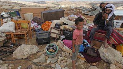 Un hombre palestino y sus dos hijos están sentados sobre los escombros de su casa destruida por el régimen de Israel.