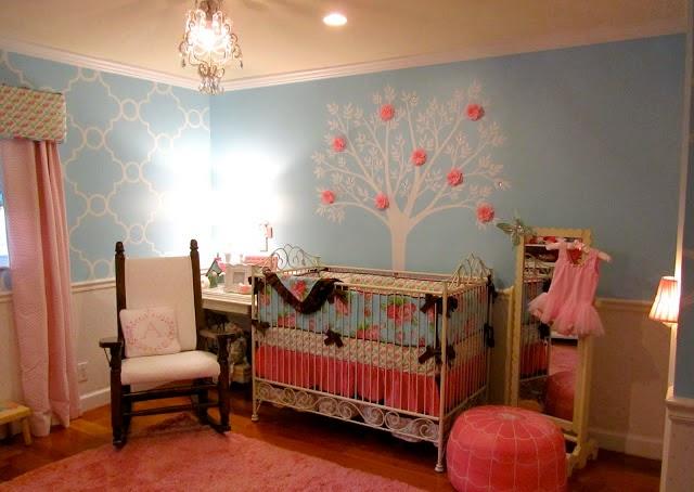quarto de bebê com parede azul e adesivos