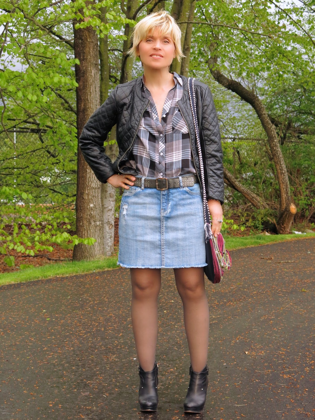 styling a distressed denim mini-skirt with a plaid shirt, quilted pleather jacket and wedge booties
