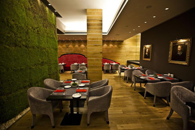 Picture of square dining tables by the green wall with living grass