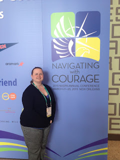 Woman standing in front of logo for NASPA 2015