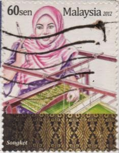woman at loom with sample of Songket fabric