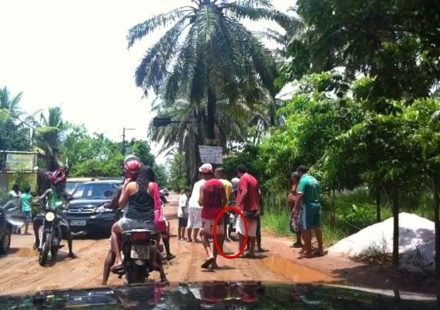 Cobra ficou enrolada no pneu da moto quando motociclista cruzou poça (Foto: Reginaldo Duarte/Divulgação)