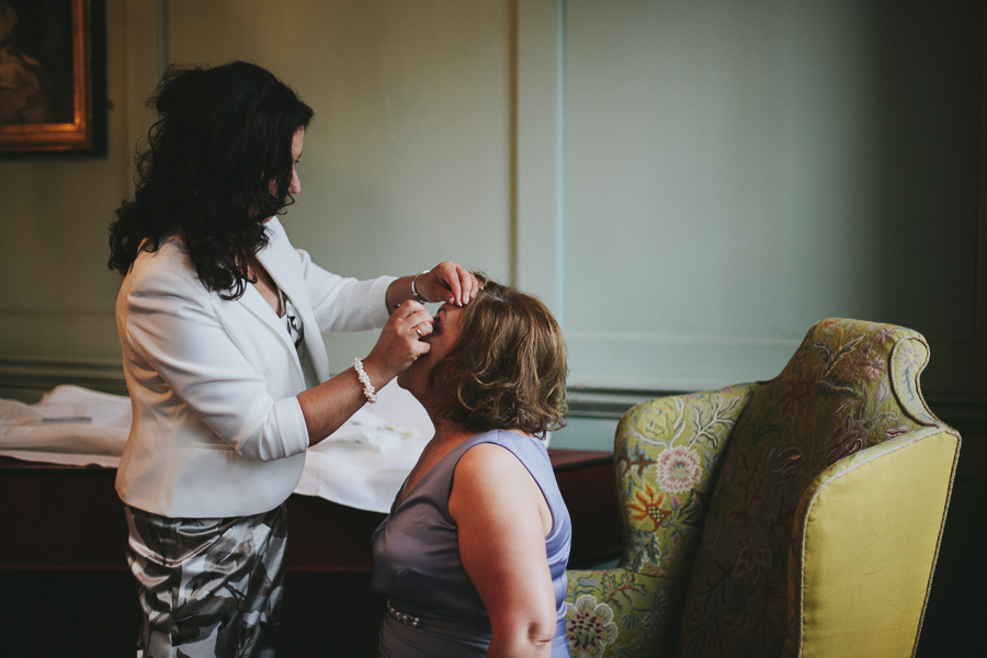 Sister of the bride and mother of the bride get ready in dark room