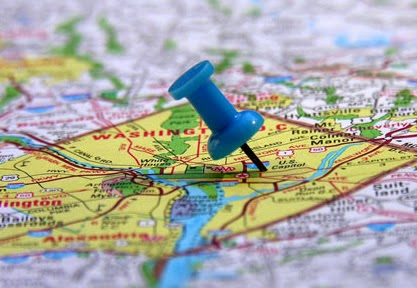 A blue pushpin sticking into a map of Washington D.C.