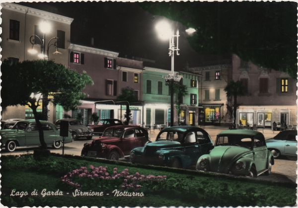 night view of small town square with parked cars