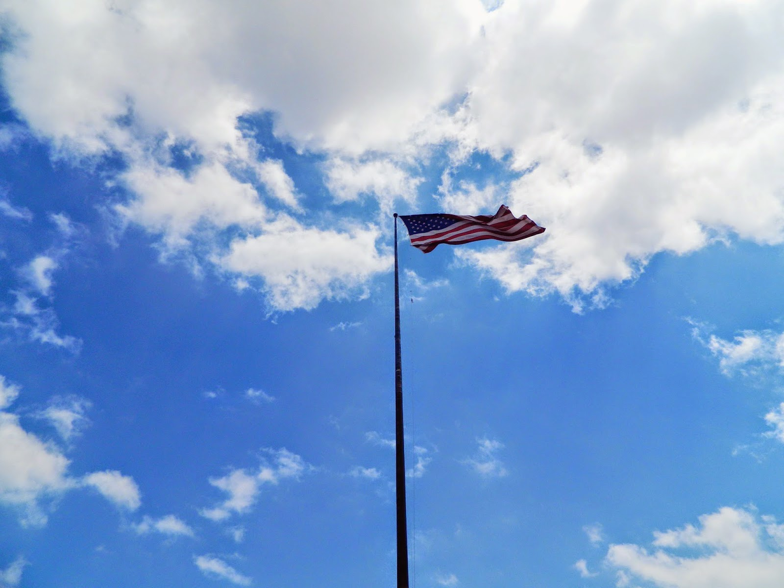 new york city american flag flying wind sky clouds