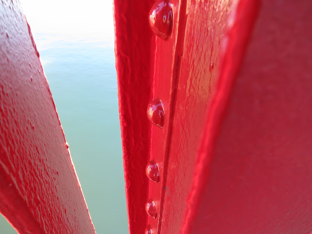 Red painted metal railings with rivets on bridge above still, pale blue water.