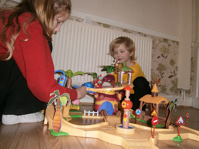 two older children playing with the jungle junction playset from flair