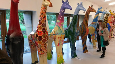 Nextra-terrestrial giraffe in line prior to Stand Tall Auction Colchester