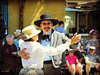 Man and woman dance in period dress at the Founder's Day event in Albuquerque's Old Town