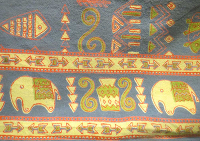 Tablecloth in blue, green, red, and cream with elephants and arrow border