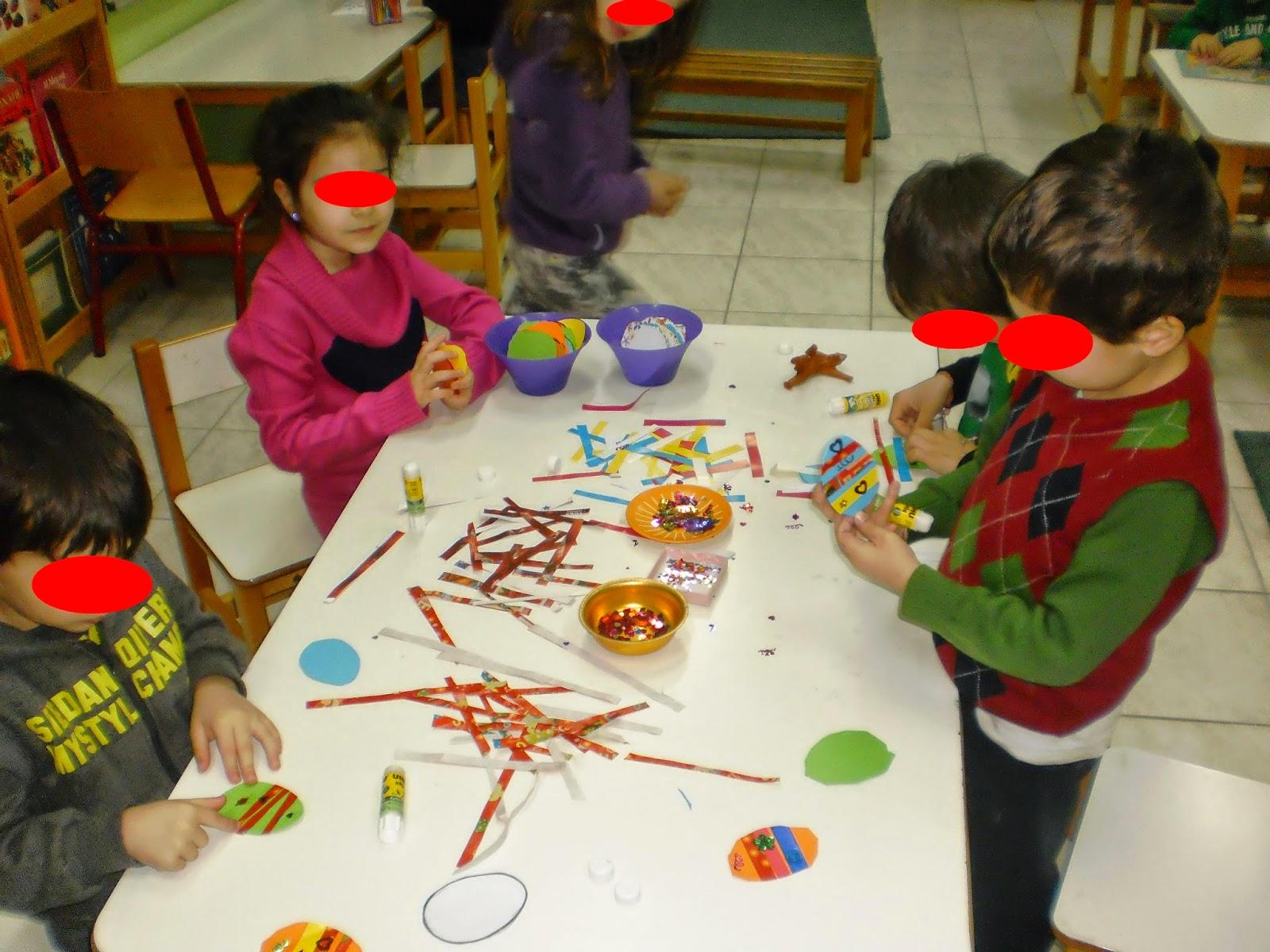 Τα παιδιά  στολίζουν χάρτνα αυγά με πουλιές και χρωματιστά χαρτιά