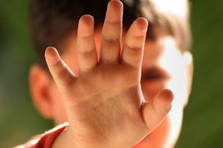 Photo illustrating child abuse with young boy holding up his hand defensively.