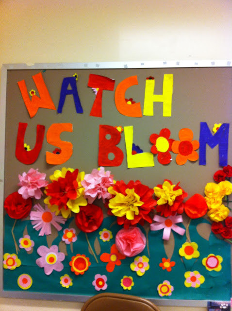 Spring themed bulletin board for school with colourful flowers and says watch us bloom
