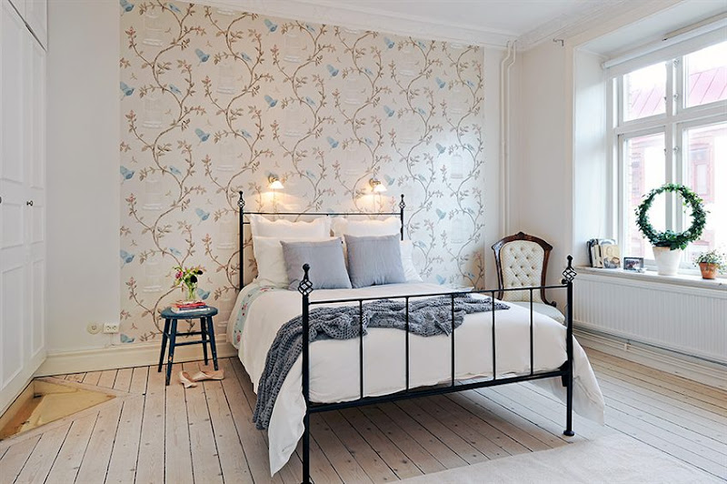 Bedroom in a Swedish apartment with iron bed frame, light knotty wood floor, an upholstered armchair, wall mounted lights, wall covered in a delicate wallpaper with a floral pattern with birdcages and a large window