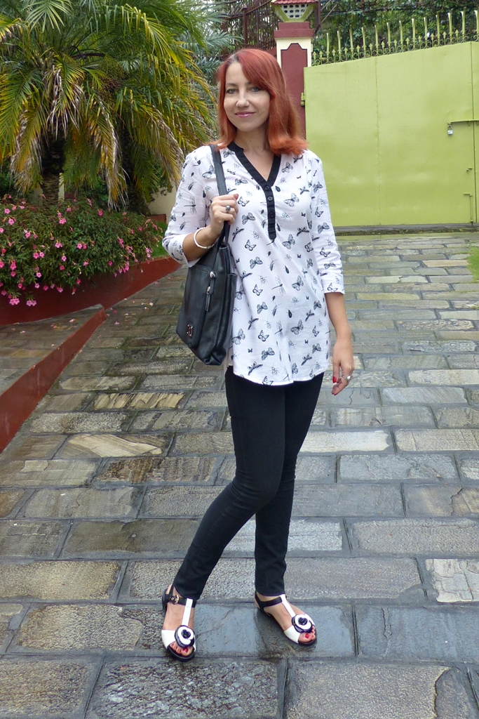Black skinnies with black-and-white bugs and butterflies tunic and black-and-white flats