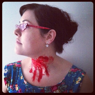 Me, wearing cats-eye glasses, pearl earrings, and a blue floral dress, with a giant neck gash.
