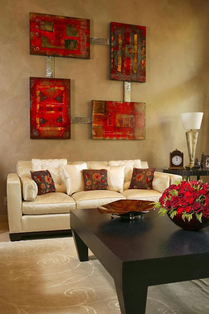 a rectangular sofa for three decorated with four contemporary wall arts